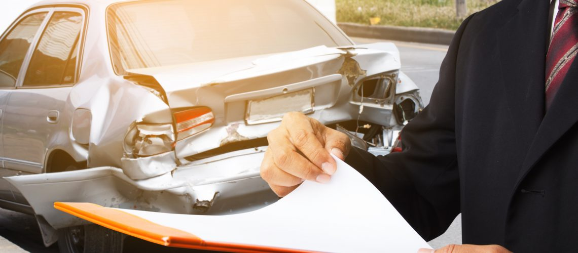 Insurance Adjuster examining a total loss vehicle